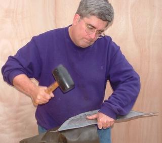 artist hammering steel sculpture